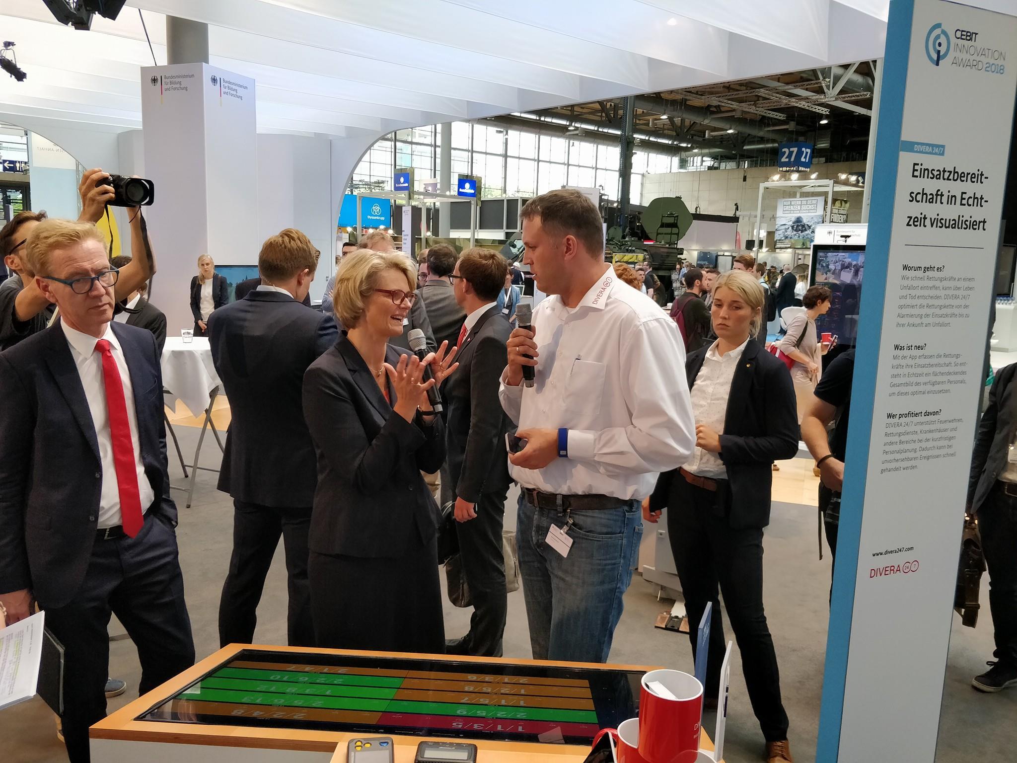 Bernhard Horst zeigt Ministerin Anja Karliczek das Exponat zur Prozessoptimierung bei Feuerwehren